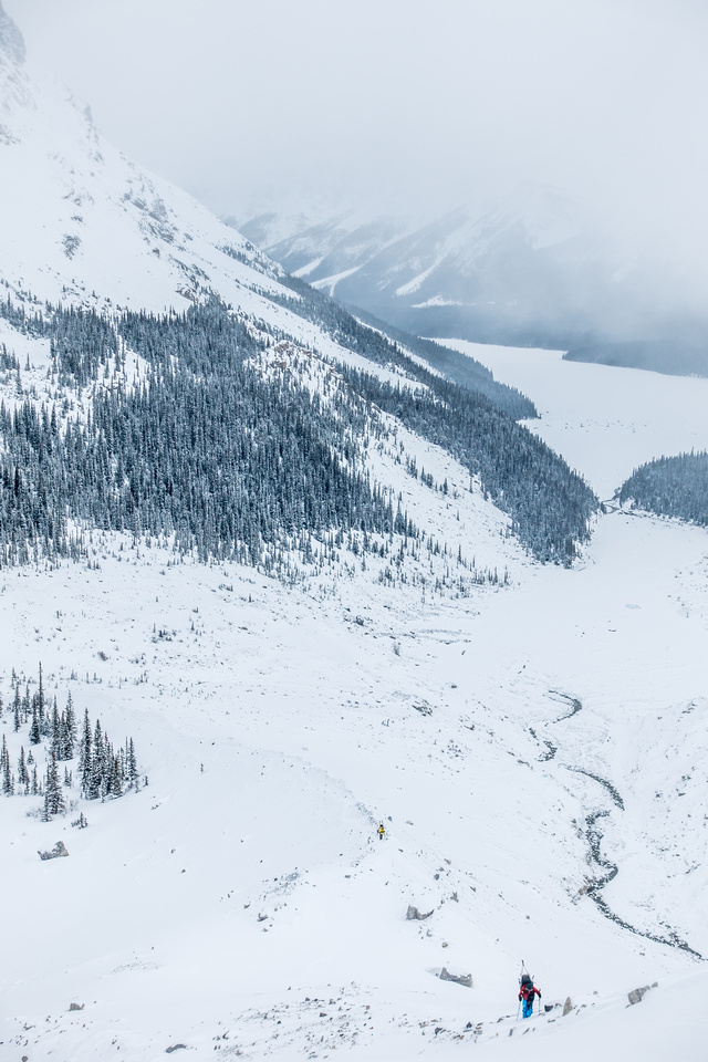 Ben is the only color showing up in the bleak morning landscape as we trudge up the moraine with our skis on our backs