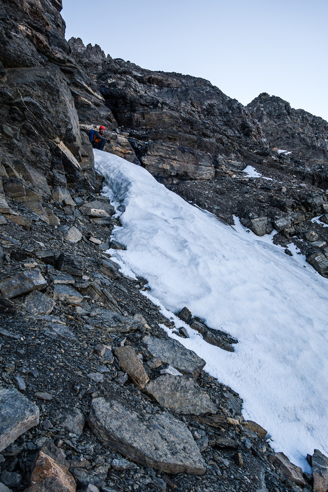 Traversing the southwest face on a mixture of snow, scree and boulders.