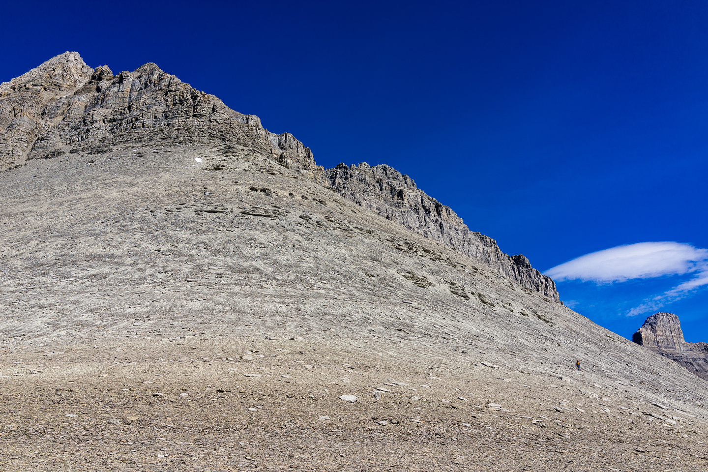 Raf looks tiny next to the huge terrain with the SW ridge rising to the NW summit at upper left.