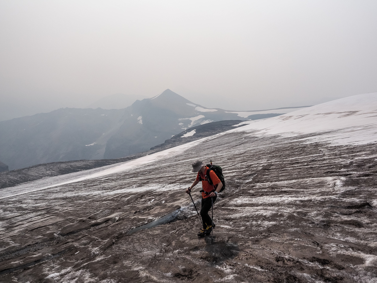 Phil crosses the glacier with Conical trying its best to show up through the choking smoke.
