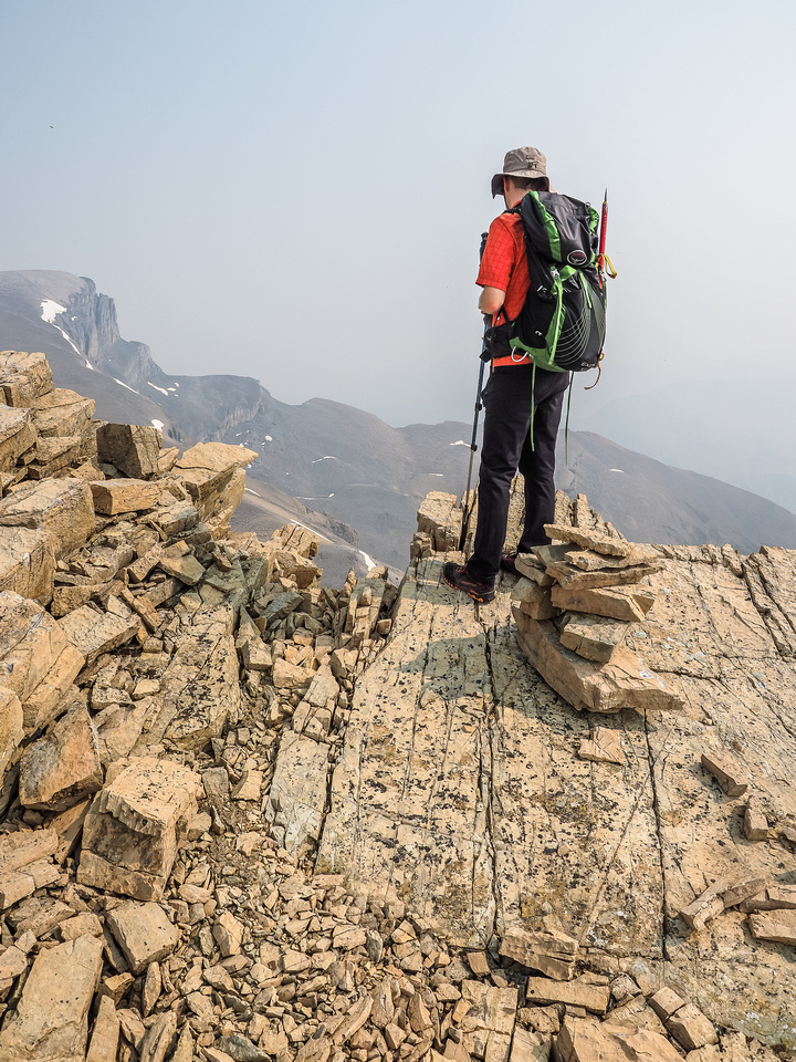 """Phil stands at the cairn marking the best descent spot over the east face of the intervening scree summit (aka """"Porcupine NE2 Peak"""")."""