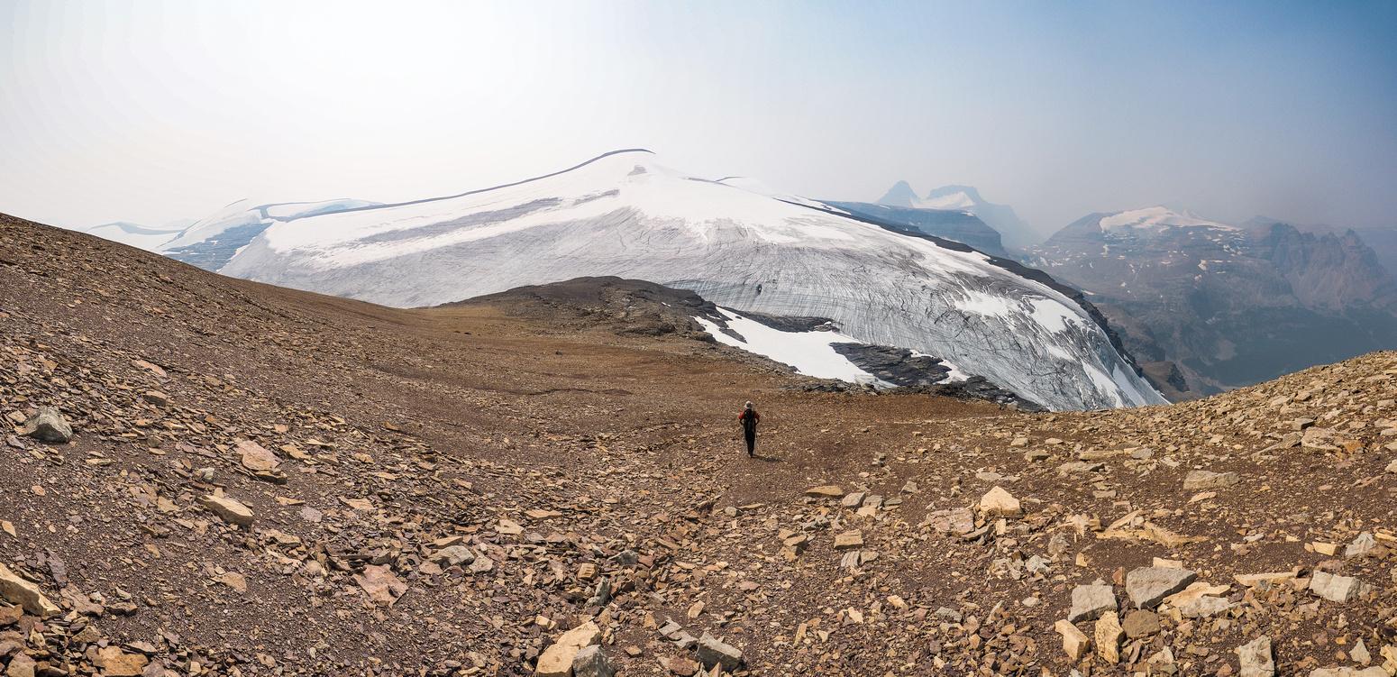 hil descends Porcupine NE2 Peak towards the glacier with Porcupine Peak looming in the far distance above him.