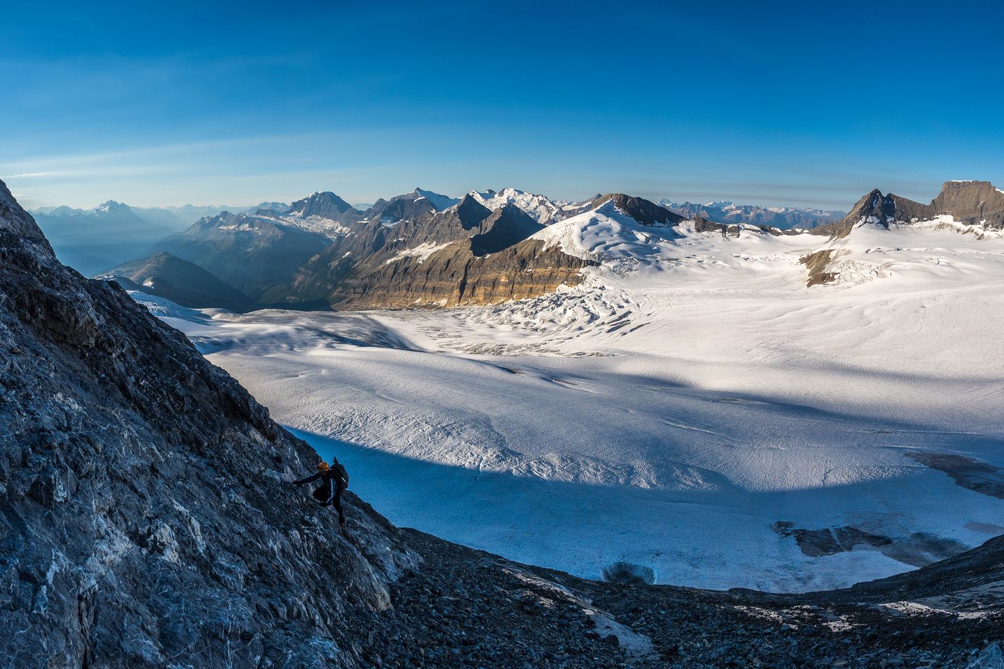 Ferenc climbs up some slabs with the Chess Group across the glacier in the background.
