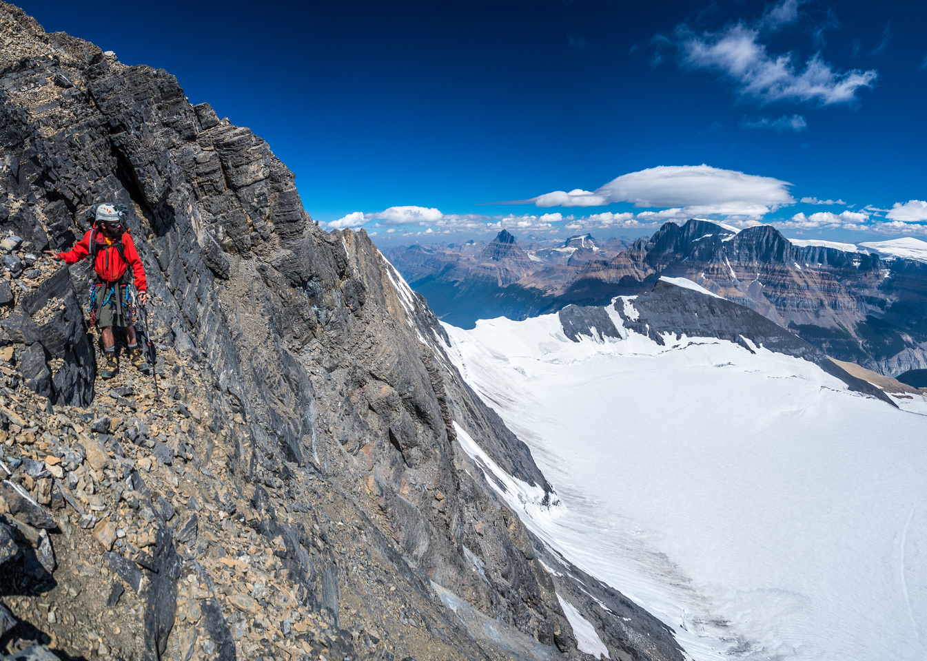 Ben near the top of the east face of the summit block with Mount Alberta, Woolley and the Twins in the distance.