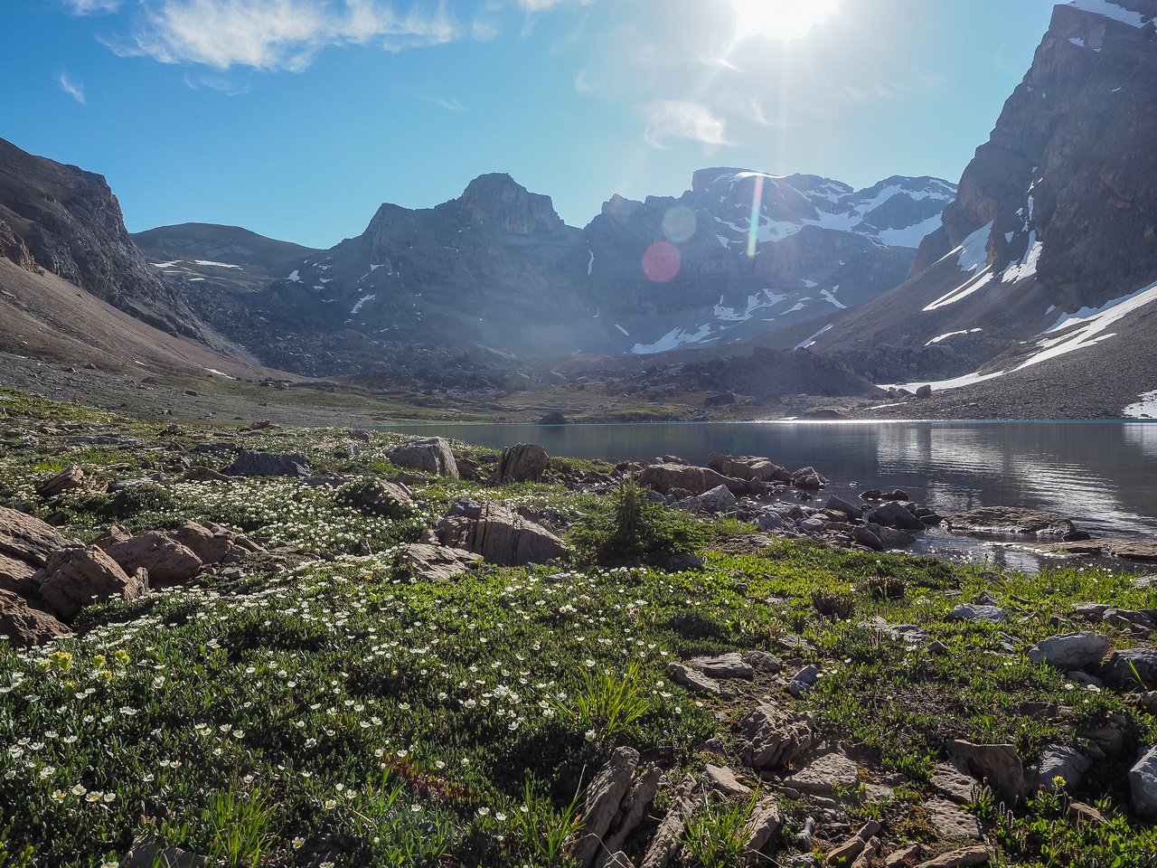 Carpets of wildflowers around Lake Alice with the blazing sun rising directly over our objective in the distance.