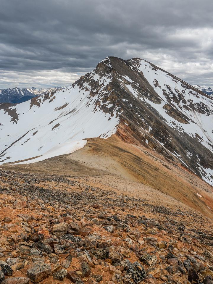 Descending colorful scree and rock towards the Two O'Clock Peak col from Landslide Peak's SE ridge.