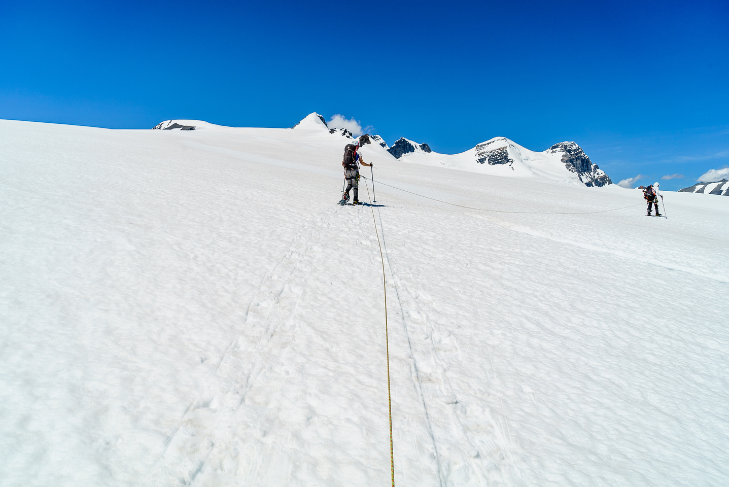 Avoiding a crevasse on the  lower south ridge of Christian Peak which rises in the far distance over Ben's head at center.