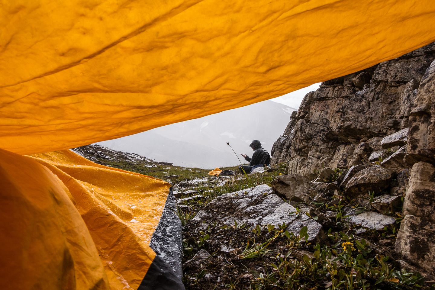 The view from under my tarp. Eric is sitting in the rain rather than get cooped up in his bivy sack already.