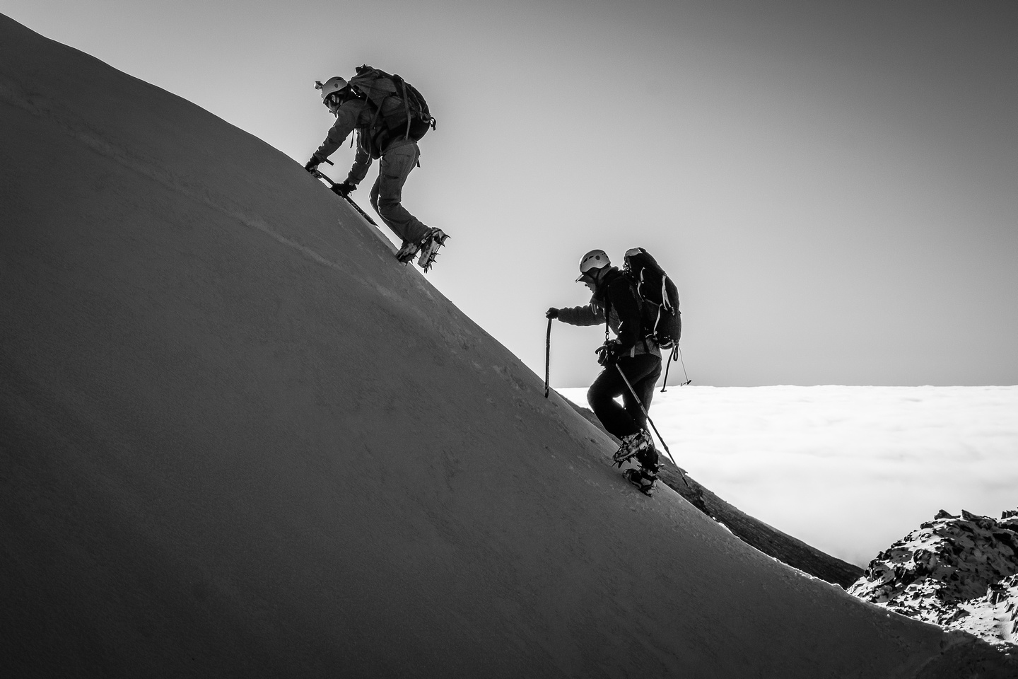Ben and Steven climb up a short, icy slope to another arete.