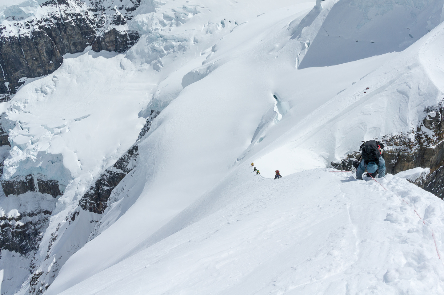 Raf's view of the two teams carefully down climbing the snow arete from the summit of Twins Tower.