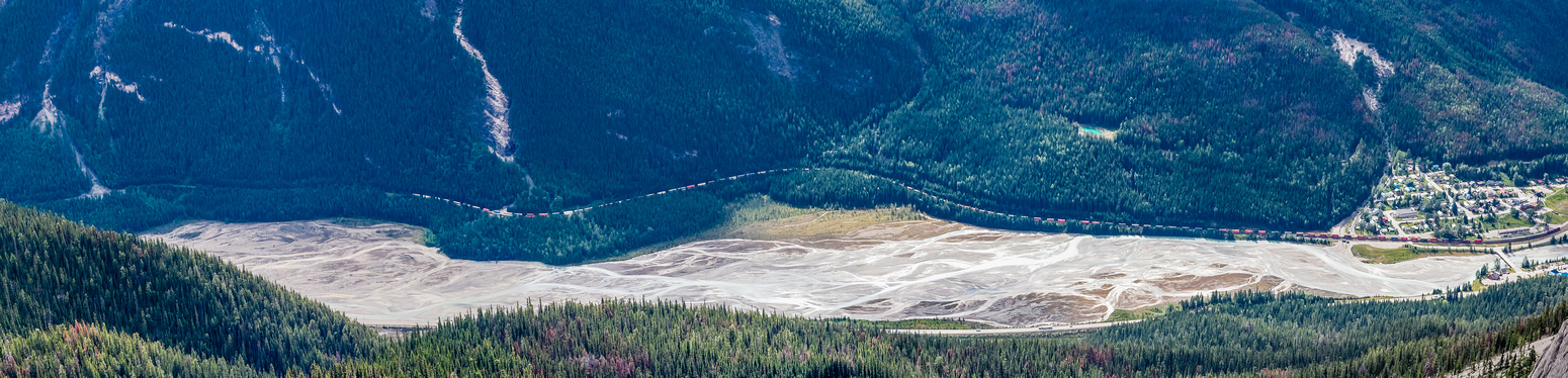 A train winds its way along the Kicking Horse River towards Field.