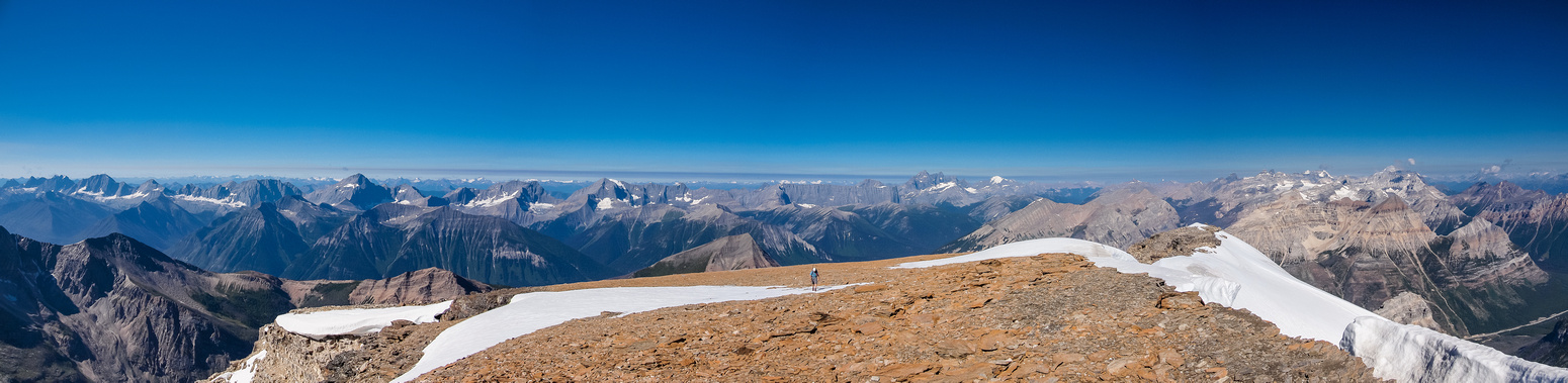 Eric works his way up the large summit plateau on Stanley - a gorgeous summit panorama opening up behind him.