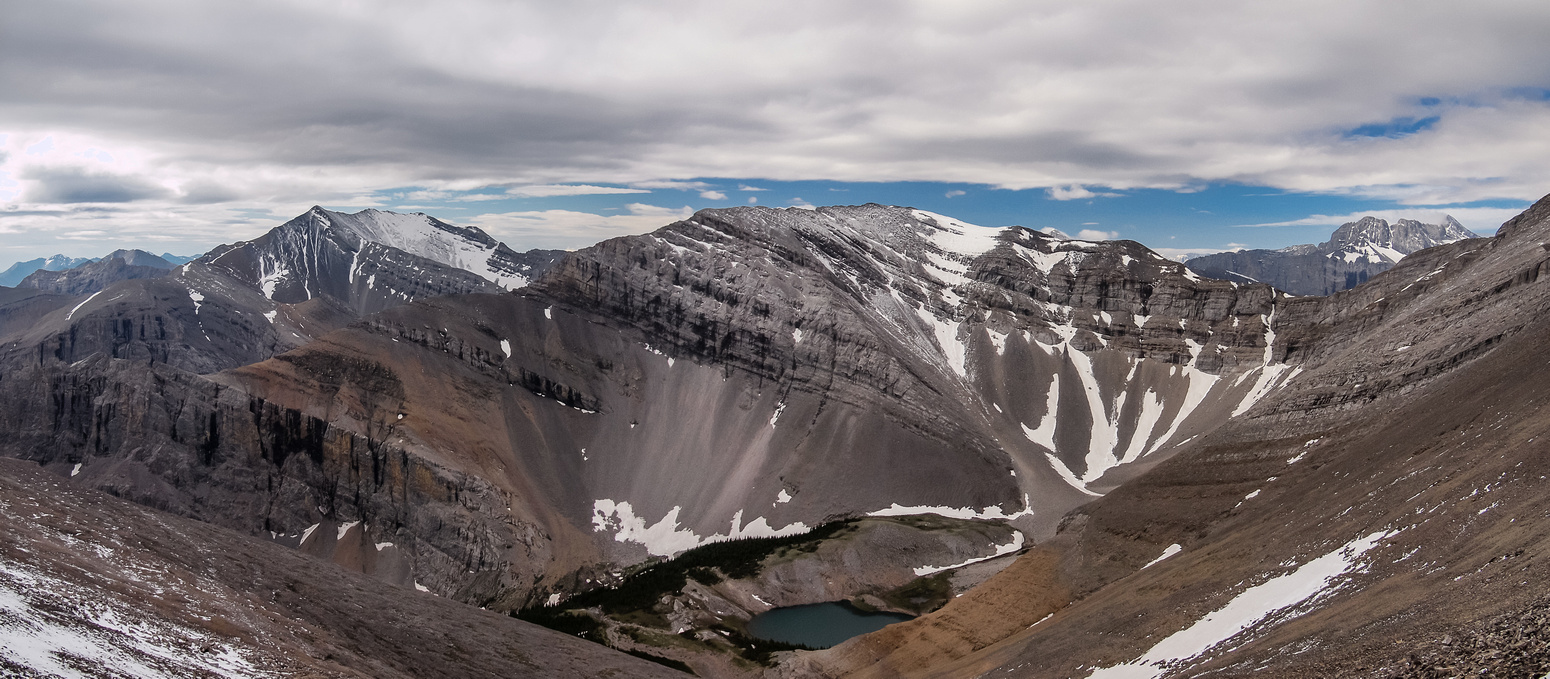A sublime alpine tarn to the south is the headwaters of Cougar Creek. Bluerock, Rose and Burns in the distance.