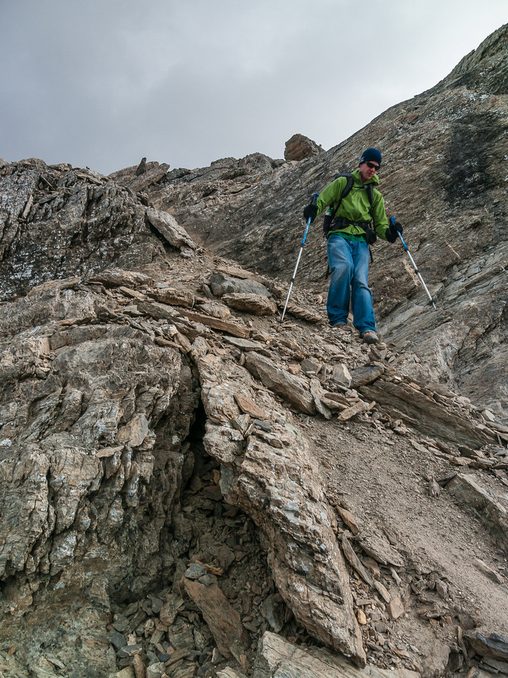Rod descends the loose, blocky terrain to the col.