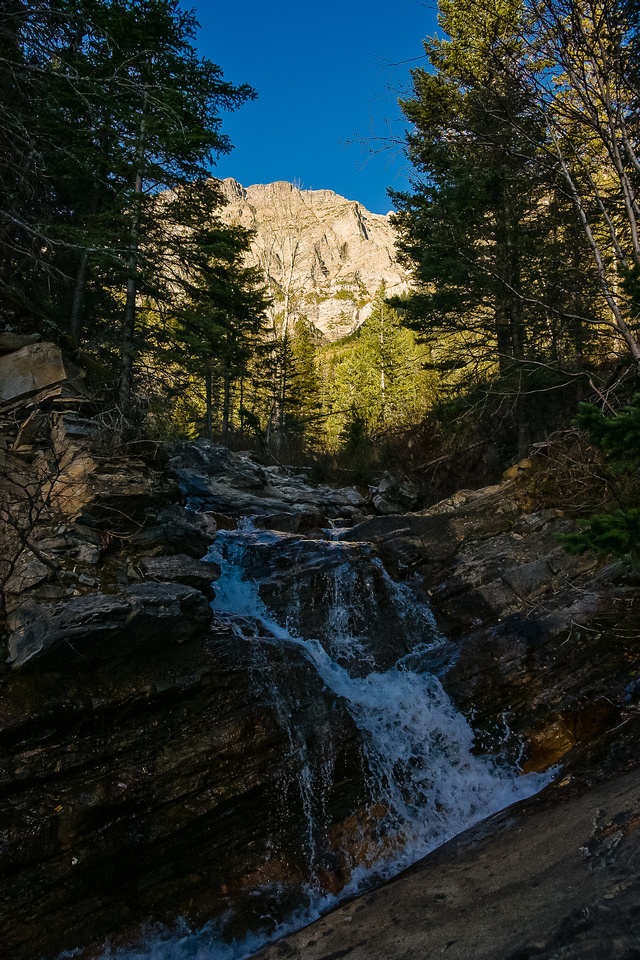 Bertha Peak rises in the morning sun behind a waterfall on the creek that cascades out of Bertha Lake