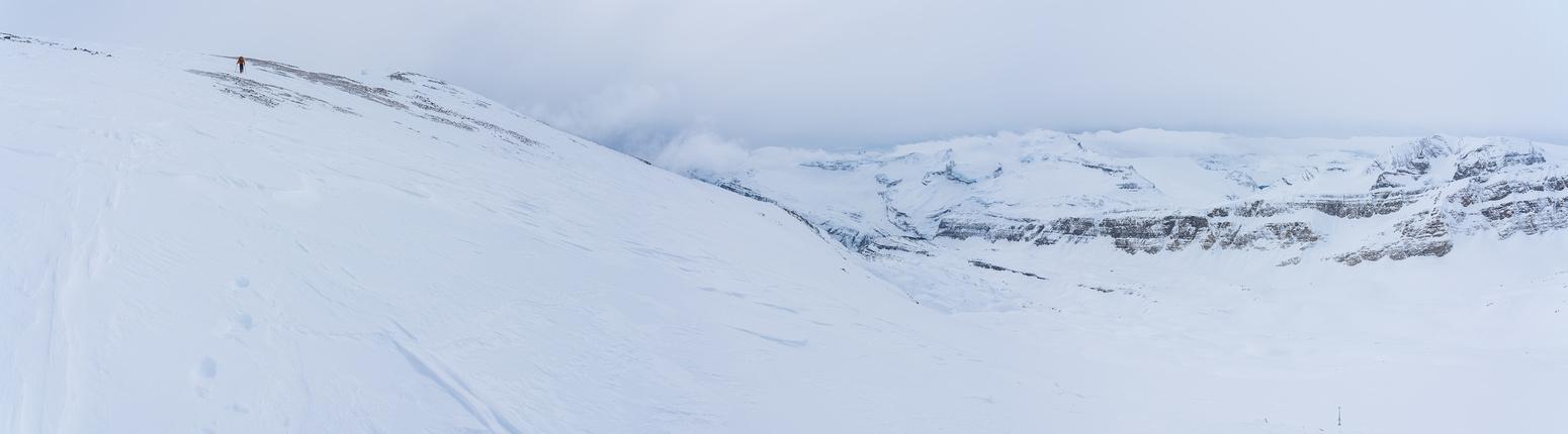 Off the skis, traversing the windblasted summit ridge to the distant summit.