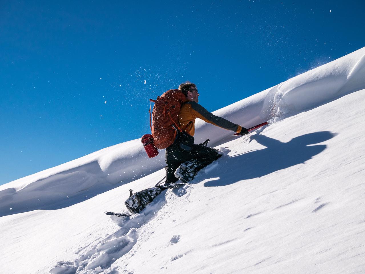 Raf chops through the cornice on the summit ridge.